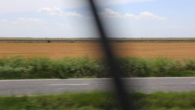 View from train in motion. And cars on the highway in the background stock footage