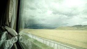 View from a train moving on the Tibetan plateau. View through the window of the Lhasa-Beijing train passes in the middle of the Tibetan plateau. View over the stock footage