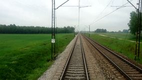 View of the Train Track from the Rear Window from the Moving Train A. Passing through Rural Area in Poland stock footage
