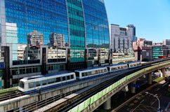 View of a train traveling on elevated rails of Taipei Metro System by a modern building of glass curtain walls on a beautiful sunn stock photo