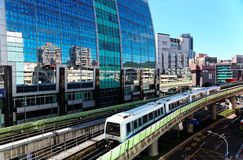 View of a train traveling on elevated rails of Taipei Metro System by a modern building of glass curtain walls on a beautiful sunn stock image