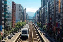 View of a train traveling on elevated rails of Taipei Metro System between office towers under blue clear sky. ! View of MRT railways in Taipei, the capital city royalty free stock images