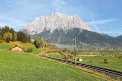 View of a train traveling through green fields with rugged Zugspitze Mountain in background on a beautiful sunny day in Lermoos, T. Irol, Austria ~ Brisk autumn Royalty Free Stock Photos