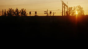 View from the train window at dawn. There are silhouettes of trees, station buildings and wagons stock footage