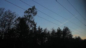 View from the train window, high-voltage wires, airplane flying in the sky. High-voltage wires stock footage