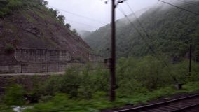 The view from the train window at the mountain river and verdant hills in the fog. Caucasus, Georgia. The view from the train window at the mountain river and stock video footage