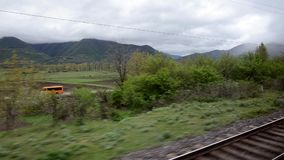 The view from the train window of the valley on a background of white clouds lying on the verdant mountains. Caucasus. Georgia. The view from the train window stock video footage