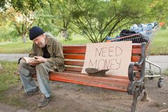 View of tramp in old dirty clothes sitting on bench reading a book. On bench old homeless beggar and board with sign need money Royalty Free Stock Photo