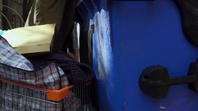 View of tramp rummaging in trash can. stock video footage