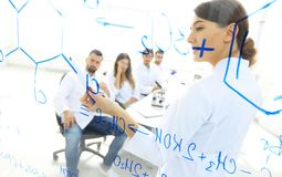 View through the transparent Board. female biochemist analyzing information. Royalty Free Stock Photos
