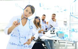 View through the transparent Board. female scientist makes a report to colleagues. Concept of research stock image