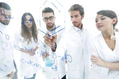 General-view seen trough a transparent board in a chemistry lab of people analyzing information stock image