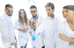 General-view seen trough a transparent board in a chemistry lab of people analyzing information Stock Images