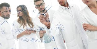 General-view seen trough a transparent board in a chemistry lab of people analyzing information royalty free stock photography