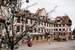 Tree branch with Christmas lights and baubles. Selective focus. Blurry building in the background. Europe. View of tree branch with Christmas lights and baubles Royalty Free Stock Photography