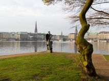View at tree and sculpture named Windsbraut, whirlwind and Binnenalster and Jungfernstieg in Hamburg, Germany. stock photos