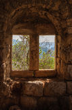 View of trees and mountains through antique window on old stone Stock Photos