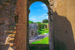 View of the Triumphal Arch of Constantine through the arch of the Colosseum. View of the Triumphal Arch of Constantine through one of the arches of the Colosseum Stock Photography