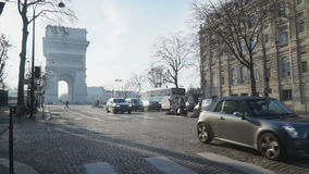 View of the triumphal arch at the end of the road. With cars and pedestrians stock footage