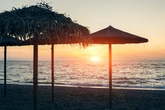 View of tropical beach with big straw umbrellas and sun loungers on the sunset sea background. View of tropical beach with big straw umbrellas and sun loungers royalty free stock photos