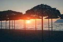 View of tropical beach with big straw umbrellas and sun loungers on the sunset sea background. View of tropical beach with big straw umbrellas and sun loungers stock images