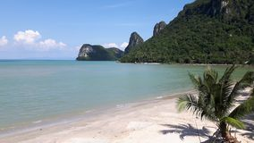 View of tropical beach and coconut trees. The green hills behind, Thailand Royalty Free Stock Photos