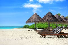 View of tropical beach with sun loungers. On summer day royalty free stock photos