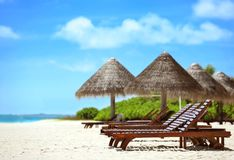 View of tropical beach with sun loungers. On summer day royalty free stock images