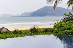 View of a tropical beach and swimming pool in Hainan island - China Royalty Free Stock Photos