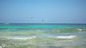 View of tropical beach. Tourists ride parasailing boat with parachute. Sailing yacht sails on waves. Turquoise water of. The Caribbean Sea. Riviera Maya Mexico stock footage