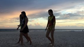 View of the tropical beach. Vietnamese women walking on the tropical beach at sunset in Phan Thiet, Vietnam stock video