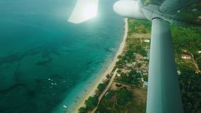 View tropical island from the passenger seat a private jet flight above clouds, sea and tropical islands. Airplane stock video