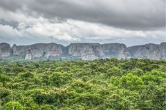 View of a tropical landscape, with forest and mountains Pungo Andongo, Pedras Negras , black stones, huge geologic rock elements. Cloudy sky as background, in royalty free stock photo