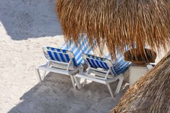 View of a tropical sandy beach with straw umbrellas and lounge chairs. Royalty Free Stock Photos