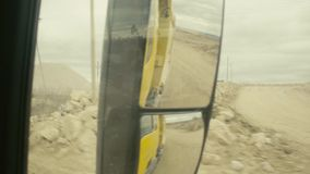 View in truck`s rearview mirror on a quarry. Point of View from truck`s rearview mirror on the road near quarry, day country side, dirt road driving. pov stock video footage