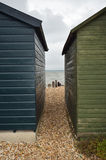 View between two beach huts. View between two wooden green beach huts from street to beach Royalty Free Stock Photo
