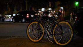 Bikes Parked on Savannah Street at Night. 9967 A view of two bicycles parked on the sidewalk on a street at night in the tourist area of Savanna, Georgia stock footage