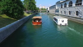 View of two boats floating on the green river in Ljubljana. stock footage