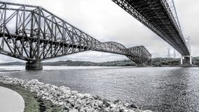 View between two bridges over the St. Lawrence River. A cloudy day before a storm in Quebec Canada royalty free stock photos