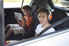 A view  on two brothers sitting in a car playing tablet and listening to music Royalty Free Stock Photography