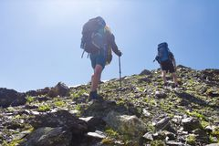 View on two climbers hike mount to peak of mountain. Leisure activity in mountains. Hiking sport in Svaneti, Georgia. Climbing royalty free stock image