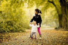 Two little girls at autumn park stock photos