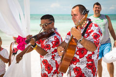 View of two musicians playing at wedding ceremony on tropical beach Stock Photography