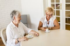 Two older women drinking coffe at home and talking stock image