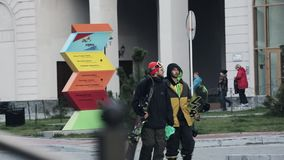 View of two snowboarders in uniform, helmets walk on street, buildings. Evening in city. Green trees stock video footage