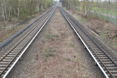 View of two train lines receding into the distance. View from the middle of two train lines or tracks receding into the distance in rural woodland in a concept Royalty Free Stock Photos
