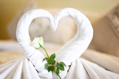 View of two white towels swans on bed sheet in hotel Stock Photos