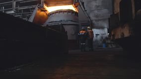 View of two workers from back in uniform and helmets on background of dark dirty factory. Footage. Two employees monitor stock photos