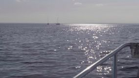 View of two yachts and sparkle on water during dusk. And good weather stock footage