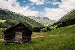 A view of typical alpine valley with rustic hut Royalty Free Stock Images